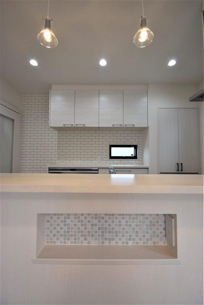 白いキッチンと水色タイルのニッチ